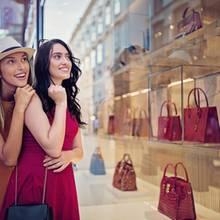 Freundinnen schauen sich Taschen im Schaufenster an