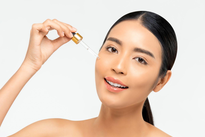 Asiatische Frau hält sich eine Pipette an die Wange
