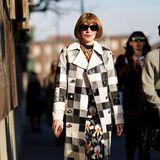 Bei der Fashion Week in Mailand macht Anna Wintour ihrem Namen als eine der einflussreichsten Frauen der Modebranche alle Ehre: Sie trägt ein Kleid mit Blumendruck,einen schwarz-weiß karierten langen Trenchcoat und stylishe Stiefel im Schlangendesign. Ihren glamourösen Look rundet sie mit einer Sonnenbrille und einer mit bunten Juwelen besetzten Statementkette ab.