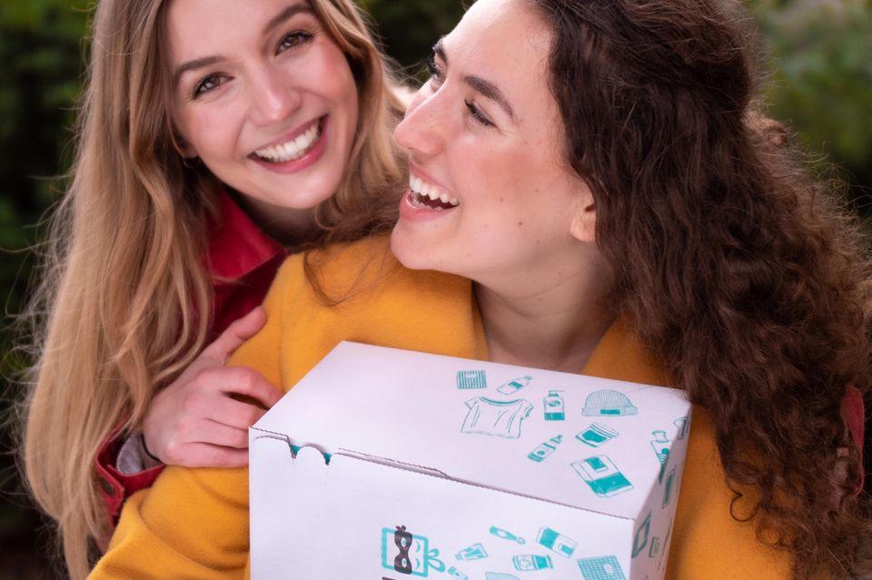 Frauen lächeln sich an und halten Box in den Händen
