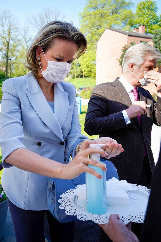 17. April 2020  Auch sie trauen sich langsam wieder aus dem Schloss: Königin Mathilde und König Philippe besuchen Abteilungen der Lütticher Klinik Centre Hospitalier Régional de la Citadelle. Vor dem Betreten zeigen sie sich verantwortungsbewusst - sie desinfizieren sich die Hände und legen Schutzmasken an.
