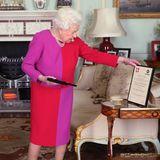 Her Royal Majesty, theColour-blocking Queen! Elizabeth II. zeigt sich inmitten der Coronakrise besonders mutig und trägt ein pink-rotes Etuikleid zur typischen Perlenkette.