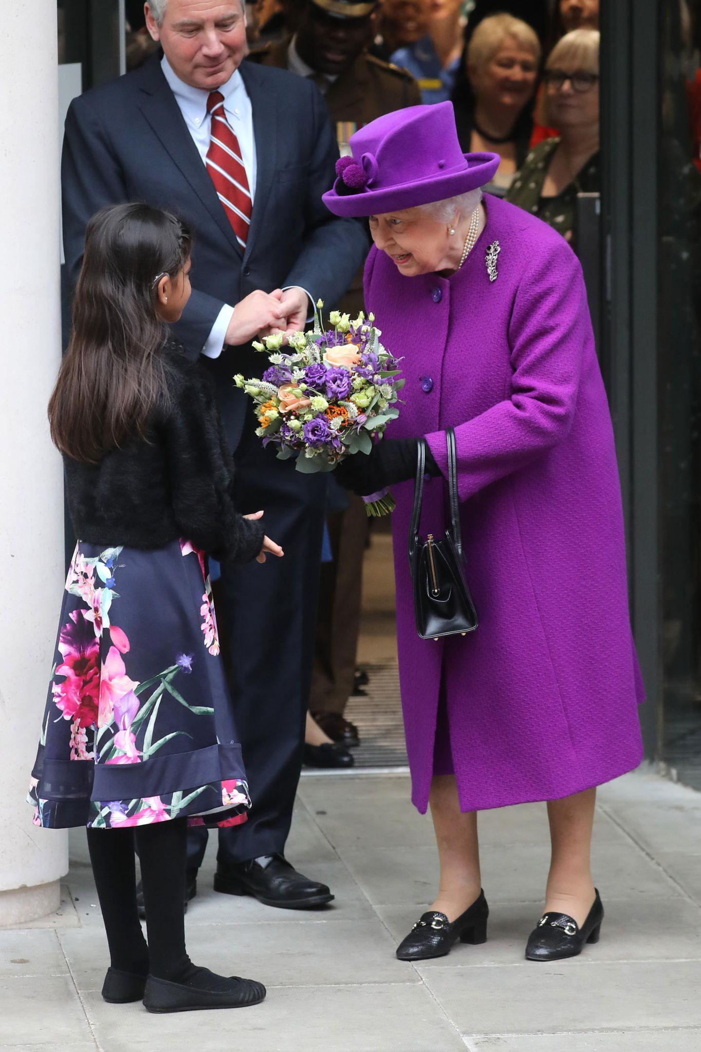Lila, der (noch lange nicht) letzte Versuch: Queen Elizabeth nimmt in leuchtendem Violett einen Blumenstrauß beim Besuch eines Londoner Krankenhauses entgegen.