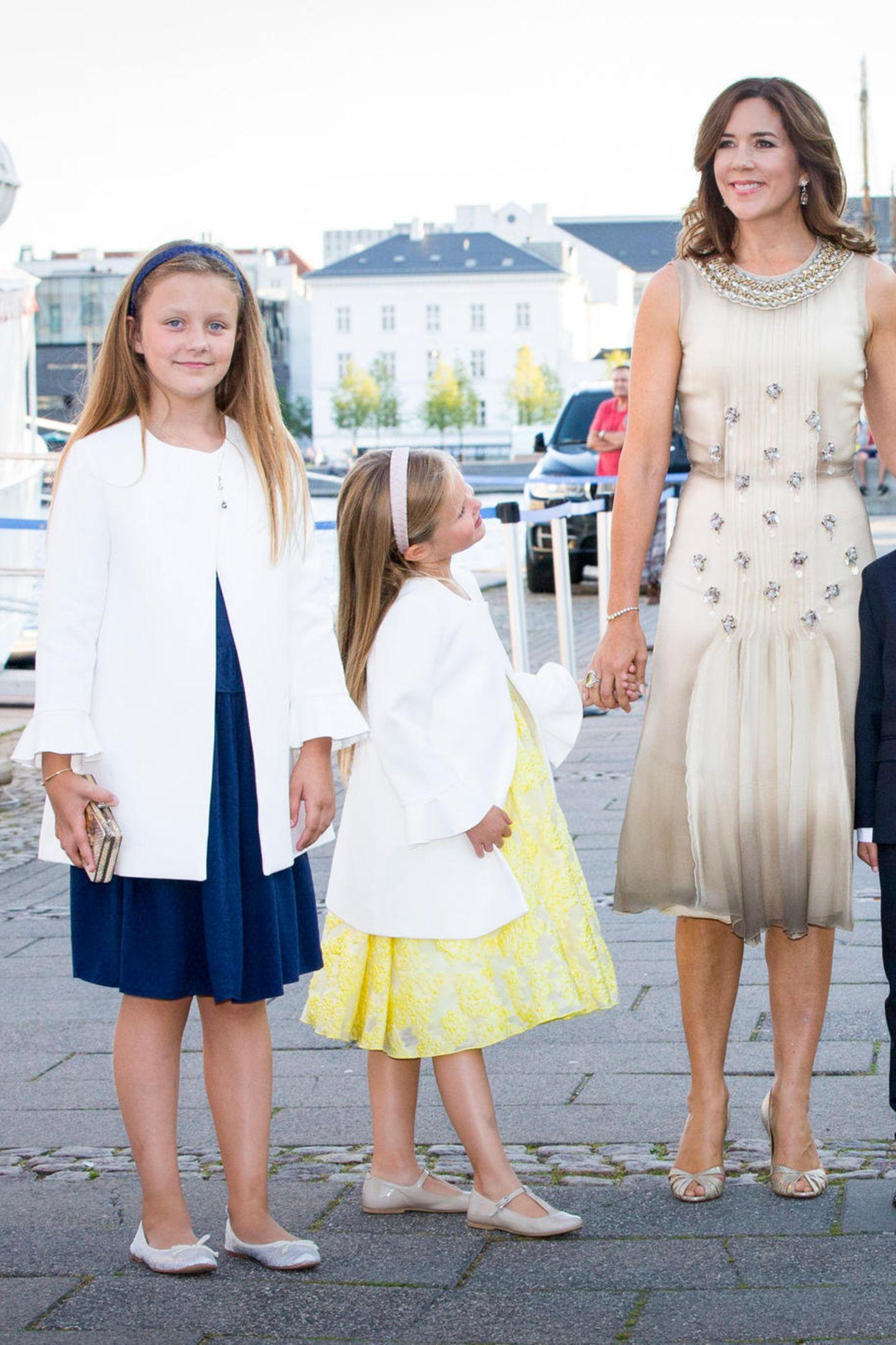 Im August 2017, mit zehn Jahren, scheint in Prinzessin Isabella von Dänemark schon die Nachwuchs-Stilikone durch. Zum dunkelblauen Sommerkleid trägt sie einen leichten, weißen Mantel mit Volantärmeln.