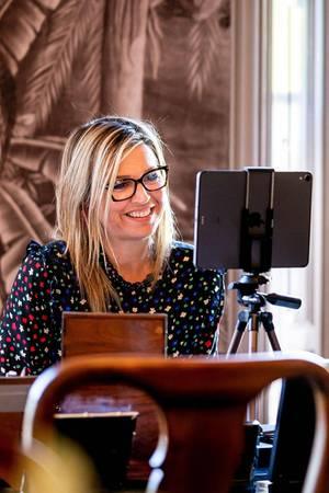 Königin Máxima lächelt im Homeoffice während einer Videokonferenz.