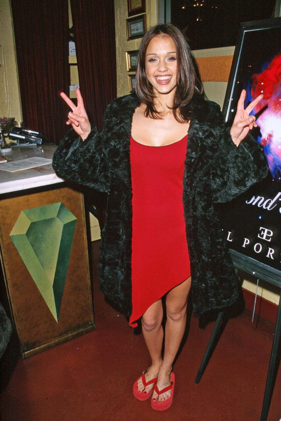 2000  Um die Jahrtausendwende herum nimmt die Schauspielkarriere von Jessica Alba immer mehr an Fahrt auf. Im Februar 2000 zeigt sie sich in einem mädchenhaften Look. Das asymmetrische rote Kleid umspielt ihre schlanke Figur.IhreHaare trägt die gebürtige Kalifornierin schulterlang und fransig geschnitten. Statt auf High Heels setzt Jessica auf lässige Flipflops.