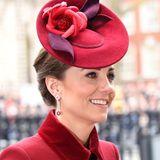 Auch Kate zeigt sich an diesem Tag mit dunkel betonten Augen und einem leichten Glow. Ihr brünettes Haar ist zu einem Dutt geknotet und lässt ihrer roten Kopfbedeckung mit floralen Applikationen so den großen Auftritt.