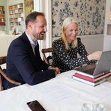 Gute Laune beim Videocall: Kronprinz Haakon und Kronprinzessin Mette-Marit von Norwegen haben in ihrem stilvollen Wohnzimmer mit eingebauten Bücherregalen und Blümchentapete sichtlich Spaß an ihrer royalen Arbeit.