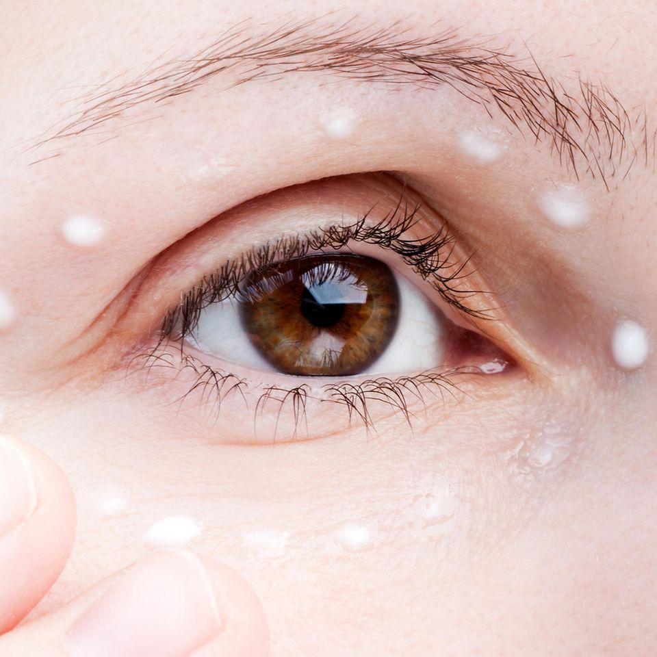 Nahaufnahme eines Auges mit Augencreme