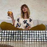 Allein zuhaus? Taylor Swift nutzt den freien Platz auf dem Sofa, um es sich mit einem Gläschen Wein auch alleine gemütlich zu machen.