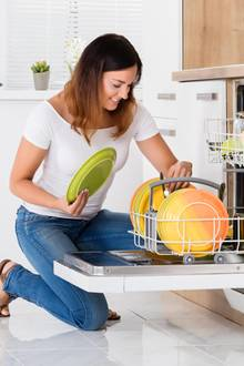Frau befüllt einen Geschirrspüler
