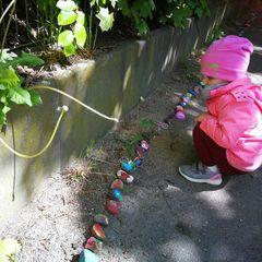 Steinschlange, bemalte Steine, kleines Mädchen schaut sich die Steinschlange an