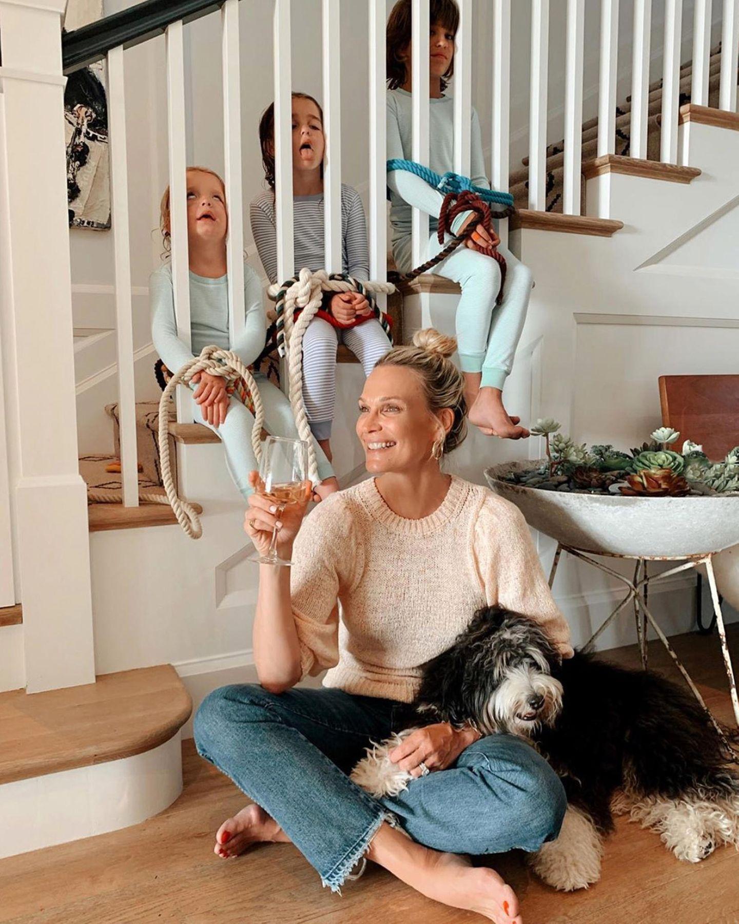 Mit einem Glas Wein in der Hand und dem Hund auf dem Schoß lässt sich der Freitagabend genießen. Und damit die Kids nicht stören, bindet Molly Sims die drei kurzerhand am Treppengeländer fest. Auch wenn das Bild mit einer großen Portion Humor genommen werden muss, sei an dieser Stelle gesagt: Bitte nicht nachmachen!