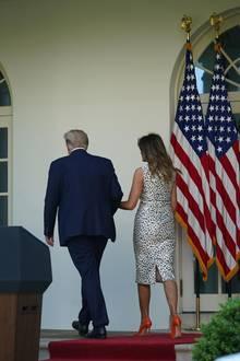 Der schlichte und körperbetonte Schnitt des Jason-Wu-Designs setzt die tolle Figur der First Lady perfekt in Szene. Dazu trägt sie Pumps von Manolo Blahnik in knalligem Orange.
