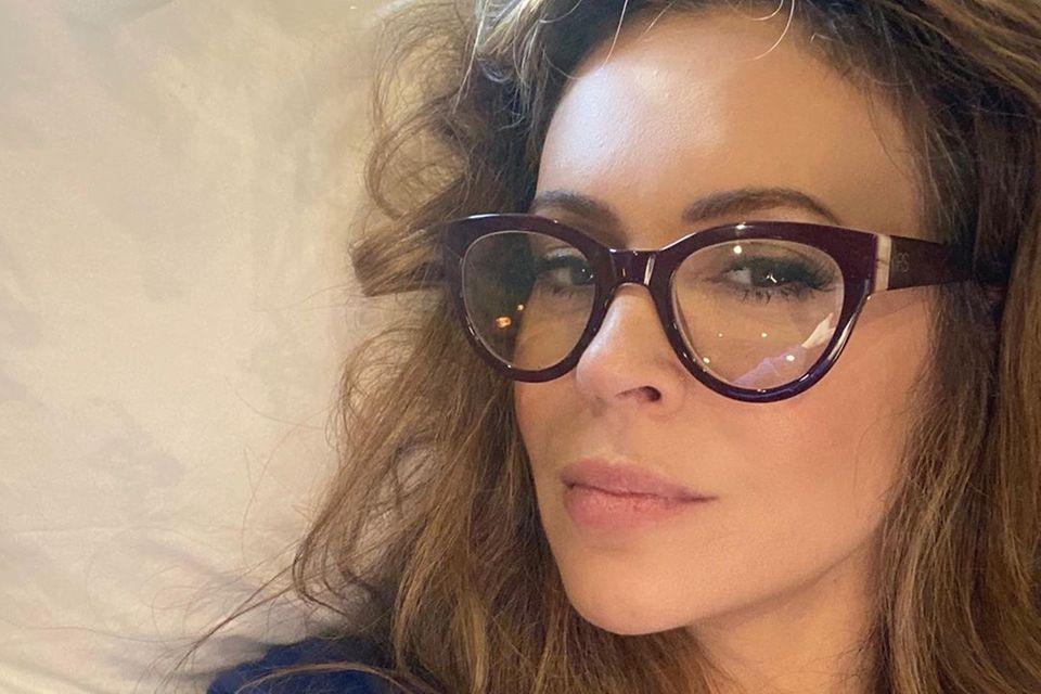 """Vintage auf der Nase! Alyssa Milano zeigt sich auf Instagram mit einer stylischen Retro-Brille, die einebreite bordeauxfarbeneFassung und goldene Applikationen aufweist. Die Brille rahmt das wunderschöne Gesicht der """"Charmed""""-Darstellerin perfekt ein."""