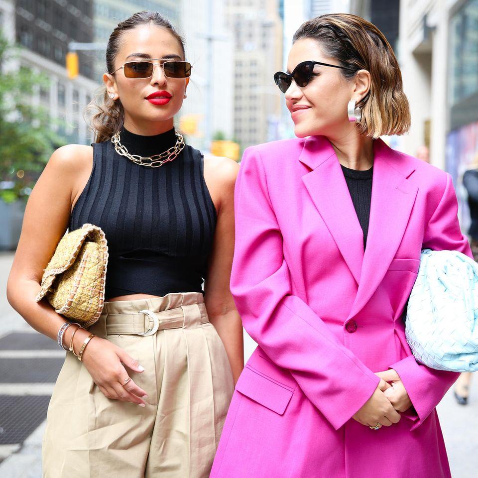Paperbag-Hose, Frau in Paperbag-Hose kombiniert mit Top, Handtasche, Sonnenbrille und Kette