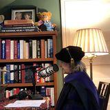 """Während Hillary Clintoneinen Podcast für """"iHeartRadio"""" aufnimmt,gewährt die ehemalige Außenministerin der USA ihren Followern einen Einblick in ihr wohnlich eingerichtetes Arbeitszimmer. Das volle Bücherregal aus Holz wird von Teddybären geziert, wobei insbesondere das Kuscheltier, das die US-amerikanische Flagge hält, ins Auge fällt. Gekrönt wird das Regal von einem Bild von Hillary und ihrem Mann Bill Clinton, während die stilvolle Vintage-Stehlampe für warme Beleuchtung sorgt. Und die bunt-geknüpfte Tischdecke rundet die Gemütlichkeit in ihremHomeofficezudem ab."""