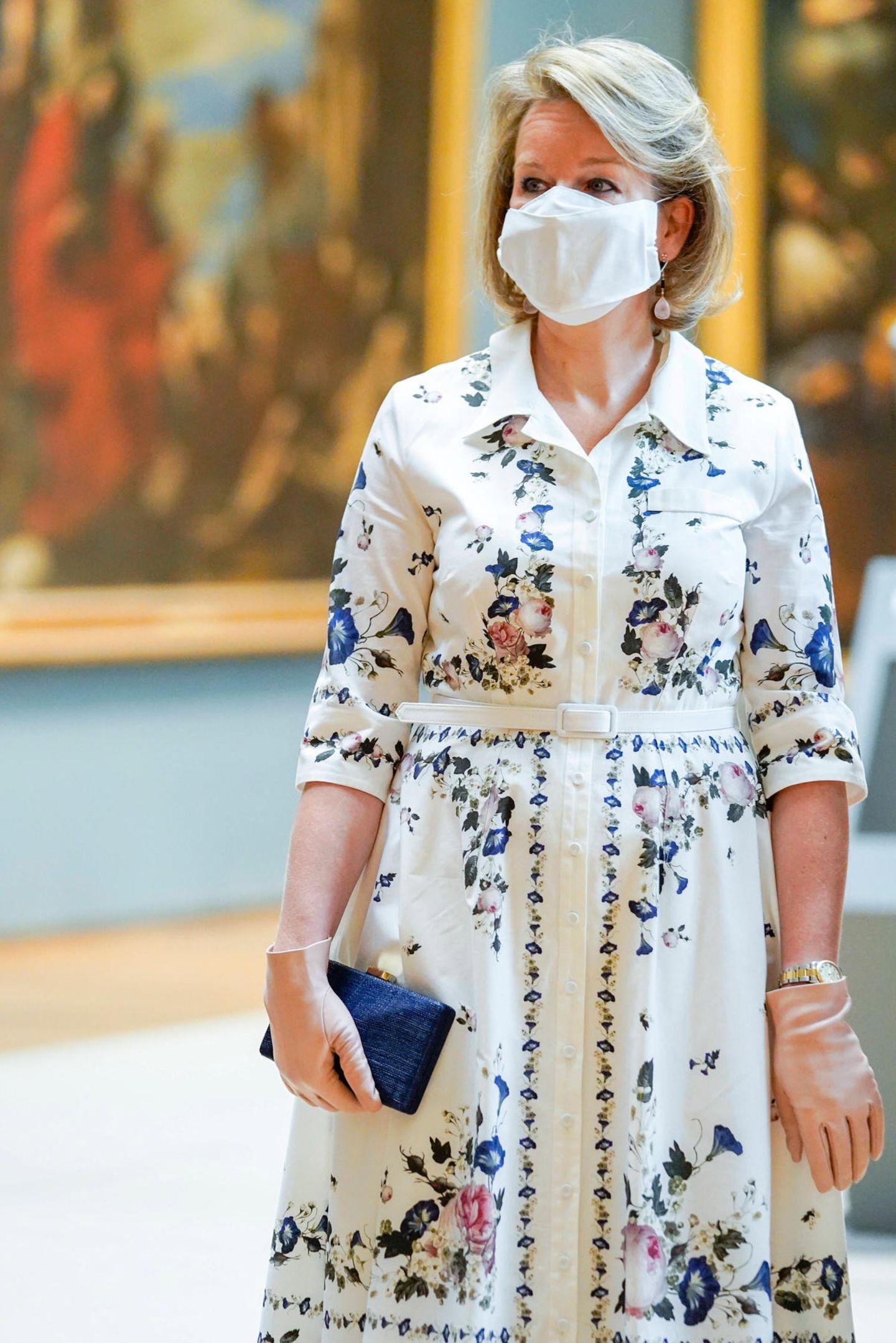 """Flower Power! Beim Besuch des """"Old Masters Museum"""" in Brüssel trägt Königin Mathilde von Belgien ein wunderschönes weißes Kleid mit buntem floralen Muster von Erdem für rund 1700 Euro. Dazu kombiniert sie eine edle, mit dunkelblauem Stoff überzogene Clutch mit goldenem Verschluss, apricotfarbene Lederhandschuhe und den momentan obligatorischen Mundschutz. Die belgische Monarchin ist jedoch nicht die Erste, die Gefallen an diesem sommerlichen Kleid findet."""