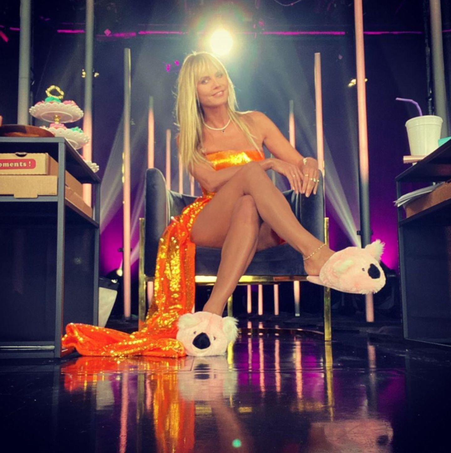 """21. Mai 2020  Hinter den Kulissen des Finales von """"Germany's Next Top Model"""" entsteht dieser lustige Schnappschuss von Heidi Klum. Im bühnenreifen Glitzer-Outfitt wartet die Model-Mama auf ihren Auftritt. Statt meterhoher High Heels zieren derweil zwei gemütliche Koala-Puschen ihre Füße. Glamourös und trotzdem bodenständig- so kennen wir unsere Heidi!"""