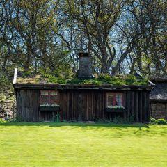 Dem Schloss gegenüber liegt das kleine,so genannte Spielhaus, das ehemals vom Gärtner und seiner Familie genutzt wurde. Es hat ein mit Gras bewachsenes Dach und ist seit 1948 die Spielhütteder Kinder der Königsfamilie.