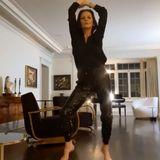 Im Klavierzimmer kann auch getanzt werden! Während dieSchauspielerin eine flotte Sohle aufs Parkett legt, zeigt sie außerdem noch mehr vonihrer stilvollen Einrichtung: Die zwei schwarzen Sessel mit Holzrahmen sehen nicht nur edel und bequem aus, sondern passen perfekt zu dem dunklen Boden. Die Kommode greift den Holzton dieser Sessel auf und wird von künstlerischen Figurengeziert, während die Bilder an der Wand für die nötige Gemütlichkeit sorgen.