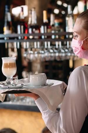 Kellnerin mit Mundschutz bringt Heißgetränke
