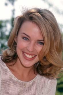 """1994 posiertKylie Minogue bei den """"World Music Awards"""" in Monaco. Ihr Markenzeichen: die strahlend blauen Augen und ihr sympathisches Lächeln. Die schöne Sängerin ist zu dem Zeitpunkt gerade erst einmal 26 Jahre alt und schon international bekannt."""