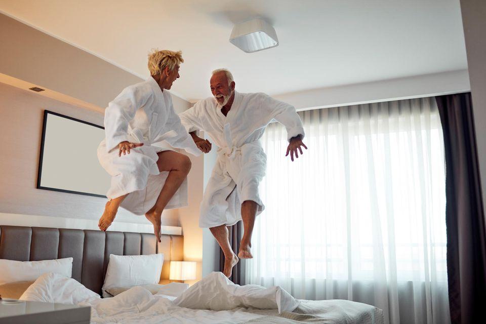 Ehepaar hüpft im Hotelzimmer auf dem Bett