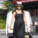 """Vogue Williams sieht einfach fabelhaft aus! In ihrem schwarzen Midi-Kleid des Labels """"The Pod Collection"""" schreitet sie mit Babykugel durch die Straßen Londons. Dazu kombiniert sie einen stylishen Strohhut, eine runde Sonnenbrille und Schuhe, die in royalen Kreisen bereits seit einiger Zeit hoch im Kurs sind. Und das beste: Es gibt sie schon für 95 Euro."""