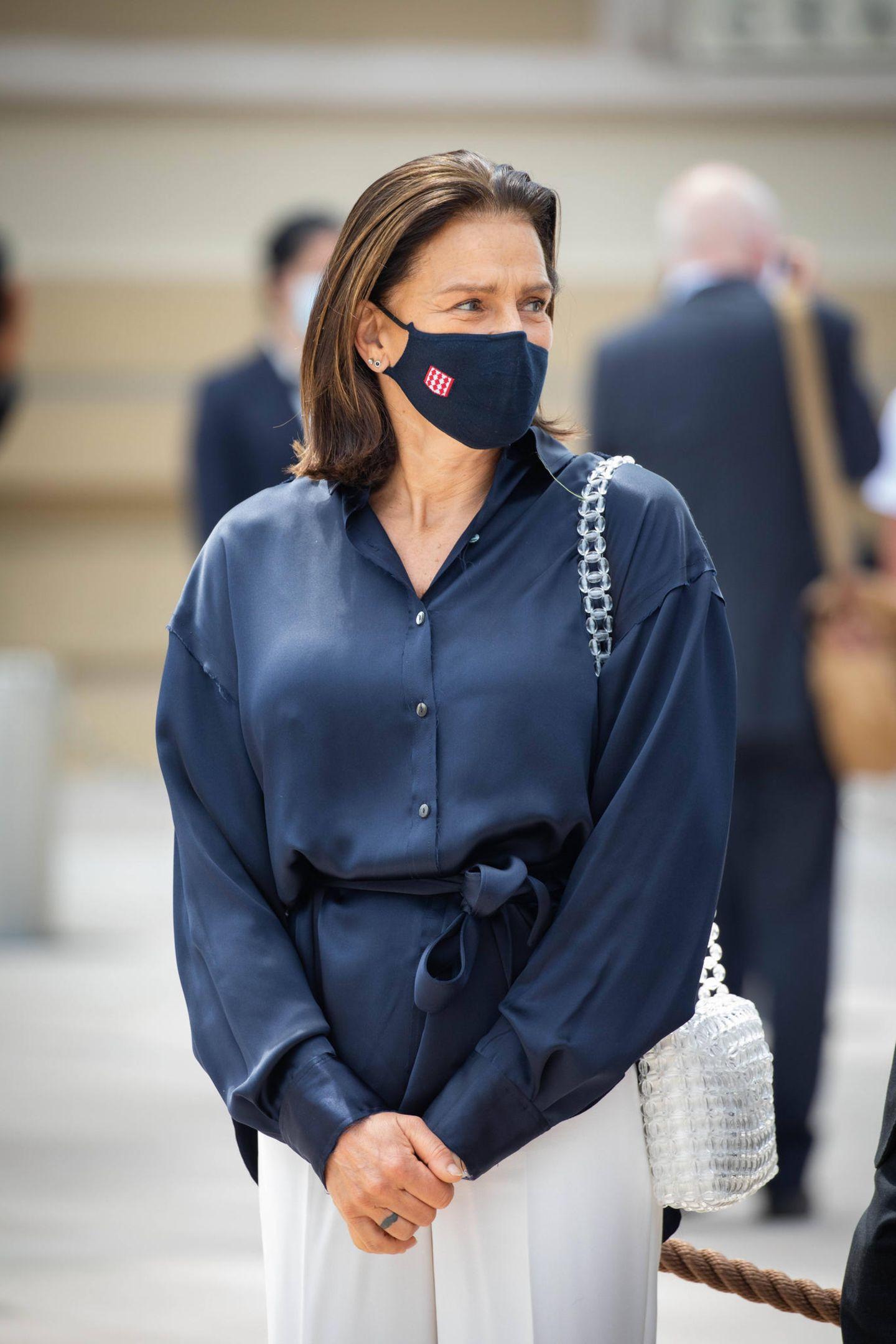 Ob hier der Mund- und Nasenschutz auf die Bluse abgestimmt wurde, oder anders herum? Prinzessin Stéphanie trägt einen luftigen Look aus lockerer dunkelblauer Bluse und cremefarbener Hose. Besonderer Hingucker ist ihre durchsichtige Tasche von Chanel, die sie sich lässig über die Schulter gehangen hat.