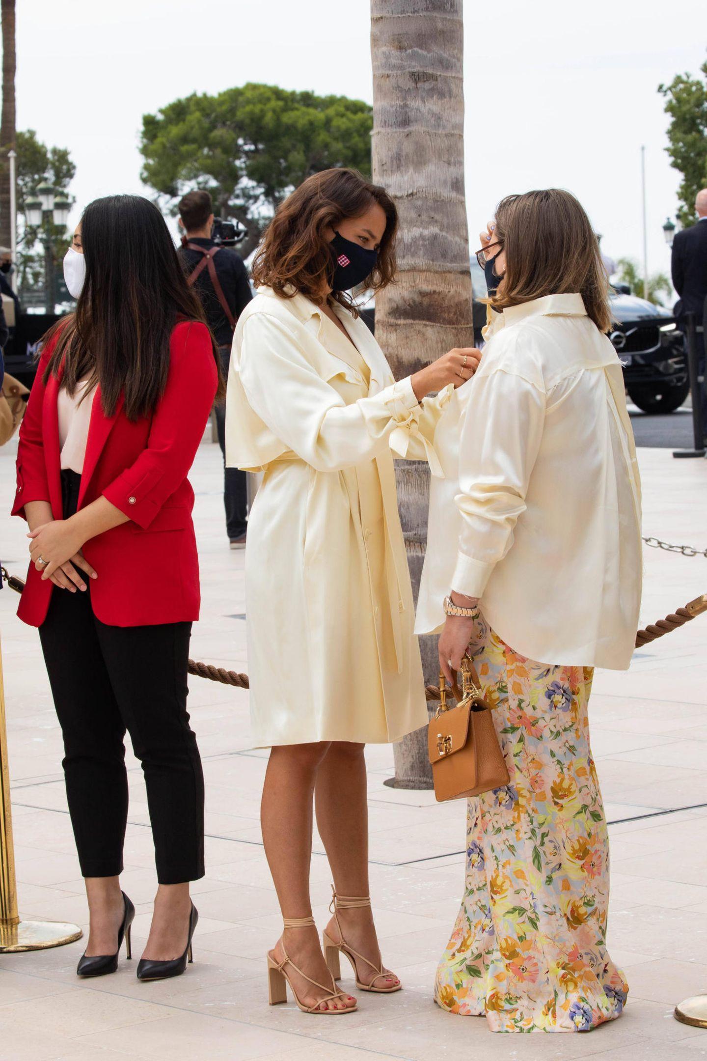 """Wenn man eine Modemacherin zur Schwester hat, lässt man sich natürlich gerne helfen: Pauline Ducruet, die mit ihrem Label """"Alter Designs"""" erste Erfolge feiert, richtet die glänzende Bluse ihrer Schwester Camille Gottlieb. Während Pauline eins ihrer eigenen Designs trägt, ein Blazer-Dress in einem zarten Gelb, entscheidet sich Camille für eine Kombi aus luftiger Blumenhose und Bluse."""