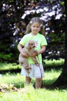 Tochter Celeste spielt mit Hündchen Lilly auf der Wiese.