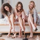 High Heels, junge, glückliche Frauen ziehen hohe Schuhe an