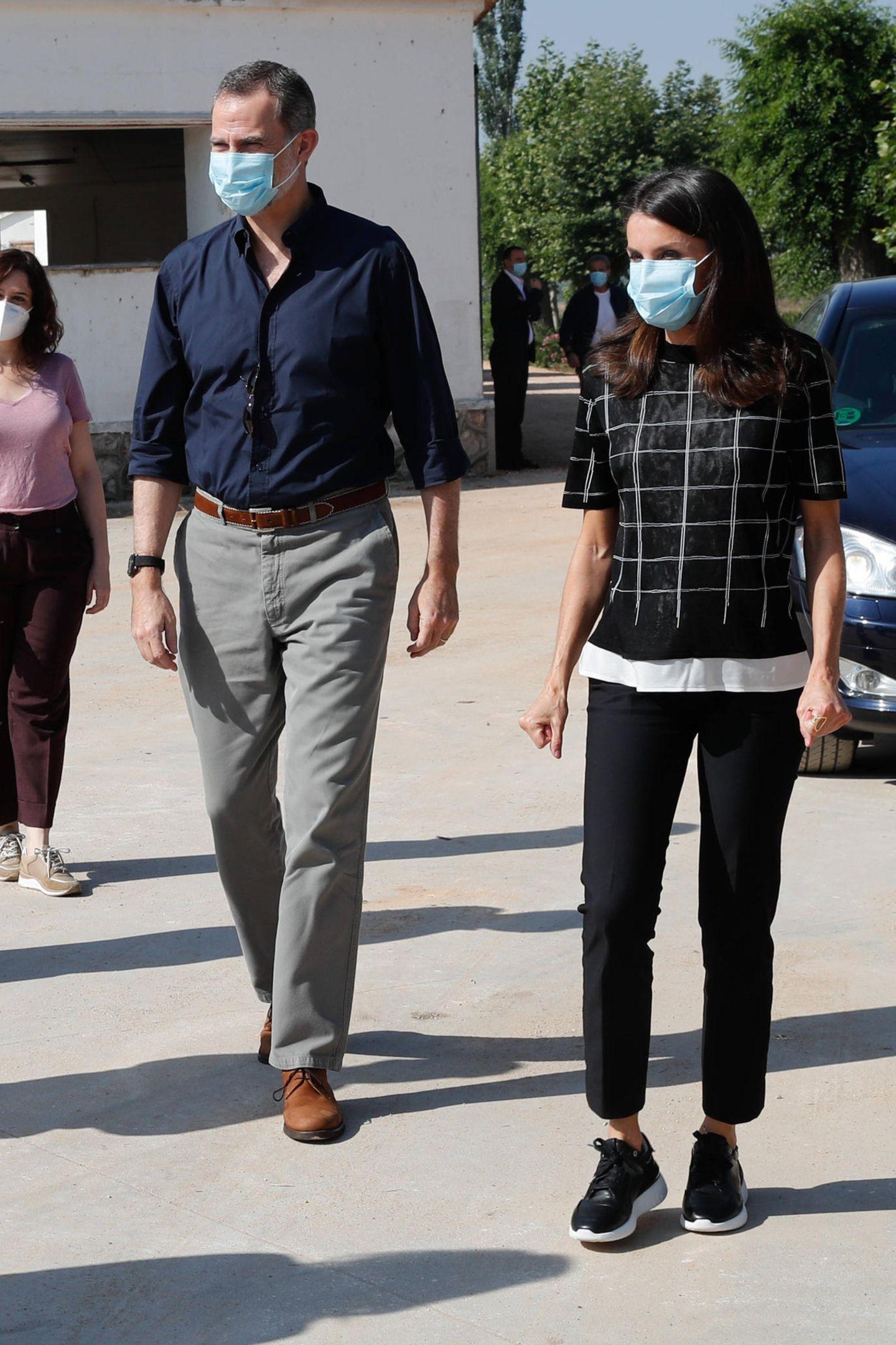 """""""Safety First"""" gilt auch beim spanischen Königspaar. König Felipe und Königin Letizia besuchen in legeren Looks einen landwirtschaftlichen Betrieb in San Martin de la Vega. Letizia trägt dabei eine schmale Hose zu Sneakern und einem dünnen Strickshirt von Hugo Boss."""