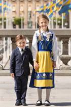6. Juni 2020  Zwar wird der Nationalfeiertag in diesem Jahr so ganz anders gefeiert als sonst, dennoch haben sich Prinz Oscar und Prinzessin Estelle für den besonderen Tag in Schale geschmissen. Estelle trägt die traditionelle Tracht in den Nationalfarben Gelb und Blau. Sie wird mit einer weißen Bluse und blickdichter Strumpfhose sowie schwarzen, flachen Lackschuhen kombiniert. Oscar hingegen posiert im schicken dunklen Anzug. Beide strahlen mit der Sonne in Stockholm um die Wette. Zuckersüß!