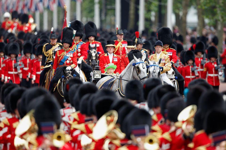 2016 ist die Queen vor lauter Soldaten in ihrer Kutsche kaum zu erkennen. Gut, dass zumindest ihr neongrüner Hut hervorblitzt. Was für ein Spektakel!
