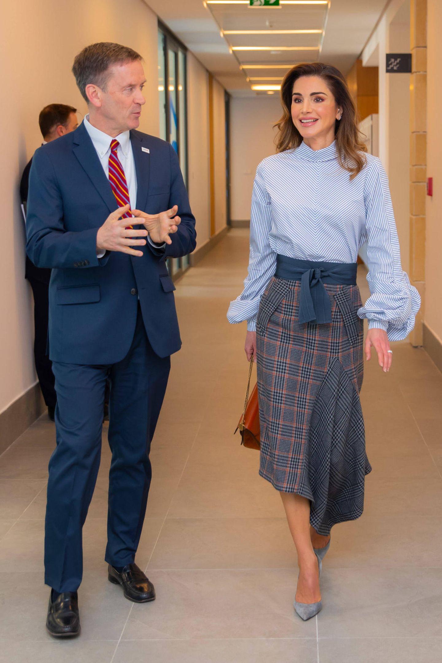 """Die gleiche hellblau gestreifte Schluppenbluse der DesignerinSilvia Tcherassi trug Königin Rania bereits im März 2019 bei einem Termin mit der Behörde für Entwicklungszusammenarbeit """"USAID"""". Was auf den ersten Blick nicht auffällt: Die Bluse hat eine Besonderheit. Bei ihr befindet sich dieklassische Schluppe und Knopfleisteam Rücken. Ja nachdem, wie man die Schluppe bindet, wirkt die Bluse strenger oder wiebeim jüngsten Auftritt seitlich gebunden, locker feminin."""