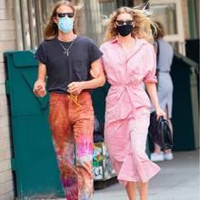 """Elsa Hosk und Tom Daly spazieren im lässigen Hippie-Style durch New York. Das """"Victoria's Secret""""-Model trägt ein rosafarbenes Hemdkleid, eine Cateye-Sonnenbrille, Sandalen und die momentane It-Clutch von Bottega Veneta (sogar ihr schwarzer Mundschutz passt perfekt zu den Accessoires) und ihr Sportler-Freund eine bunte Batikhose zum grauen Shirt. Der perfekt aufeinander abgestimmte Pärchen-Style kommt nicht von ungefähr. Im Interview mit der australischen Vogue hat die gebürtige Schwedin mal gesagt, dass sie eine Menge Klamotten mit ihrem Freund teile."""