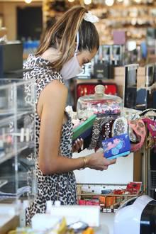 Was gibt's denn hier Schönes? Alessandra Ambrosio, mit Maske kaum zu erkennen, stöbert in einer Boutiquein Santa Monica nach Beauty-Produkten.