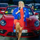 Ein hautenges Dress in Ferrarirot setzt die Kurven der Sängerin perfekt in Szene. Dazu trägt Beatrice eine kurze Lederjacke in sattem Blau mit schwarz-weißen Highlights, die an die Zielfahne eines Autorennens erinnern.