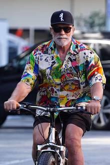 Rad-Fan Arnold Schwarzenegger dreht ganz regelmäßig seine Runden in L.A., doch so farbenfroh sieht man ihn selten. Nicht nur auf der Schirmmütze ist ein Bodybilder-Image zu sehen, das ganze Shirt ist mit bekannten Bodybuildern bedruckt. Auf seiner rechten Seite prangt ganz prominent ein schwarz-weiß Foto aus seiner eigenen aktiven Zeit.