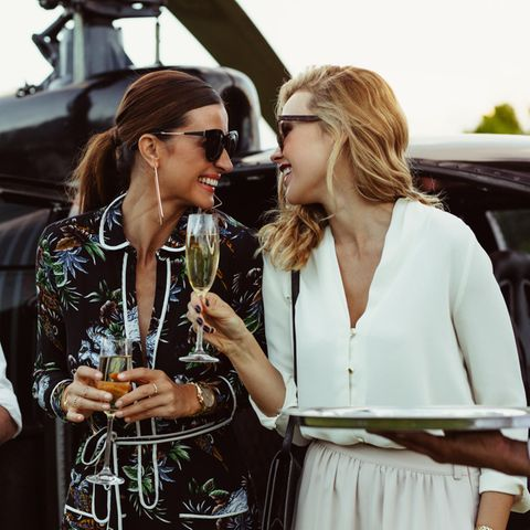 Zwei Frauen stehen lachend vor einem Hubschrauber