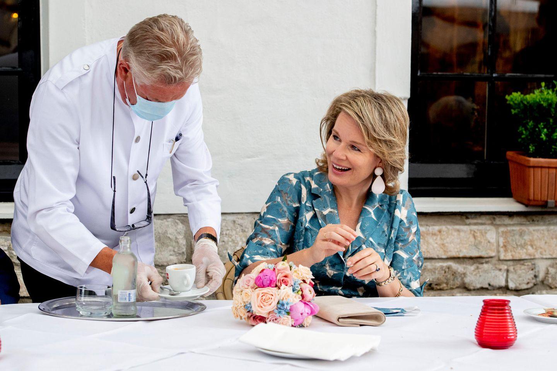 """16. Juni 2020  Schließlich entscheidet sie sich, ihn einfach abzunehmen. Auf der Terrasse eines Horeca-Unternehmens (kurz für """"HOtel, REstaurant, CAfé"""") genießt die Königin eine Tasse Kaffee und spricht mit Vertretern der Branche über die Auswirkungen der Coronakrise."""