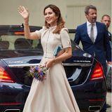 Kronprinzessin Mary strahlt am 80. Geburtstag ihrer Schwiegermutter Königin Margrethe in einem nudefarbenen Kleid mit Taillengürtel von Beulah London elegante Zurückhaltung aus. Eine farbenfrohe Clutch sowie der kleine, fröhliche Blumenstrauß ergänzen ihren femininen Look perfekt.