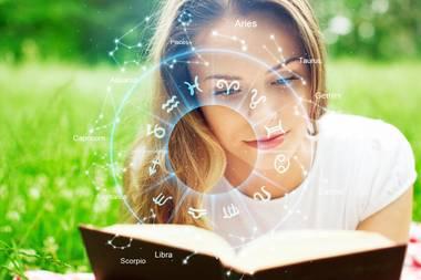 Mädchen liest Buch über Horoskope