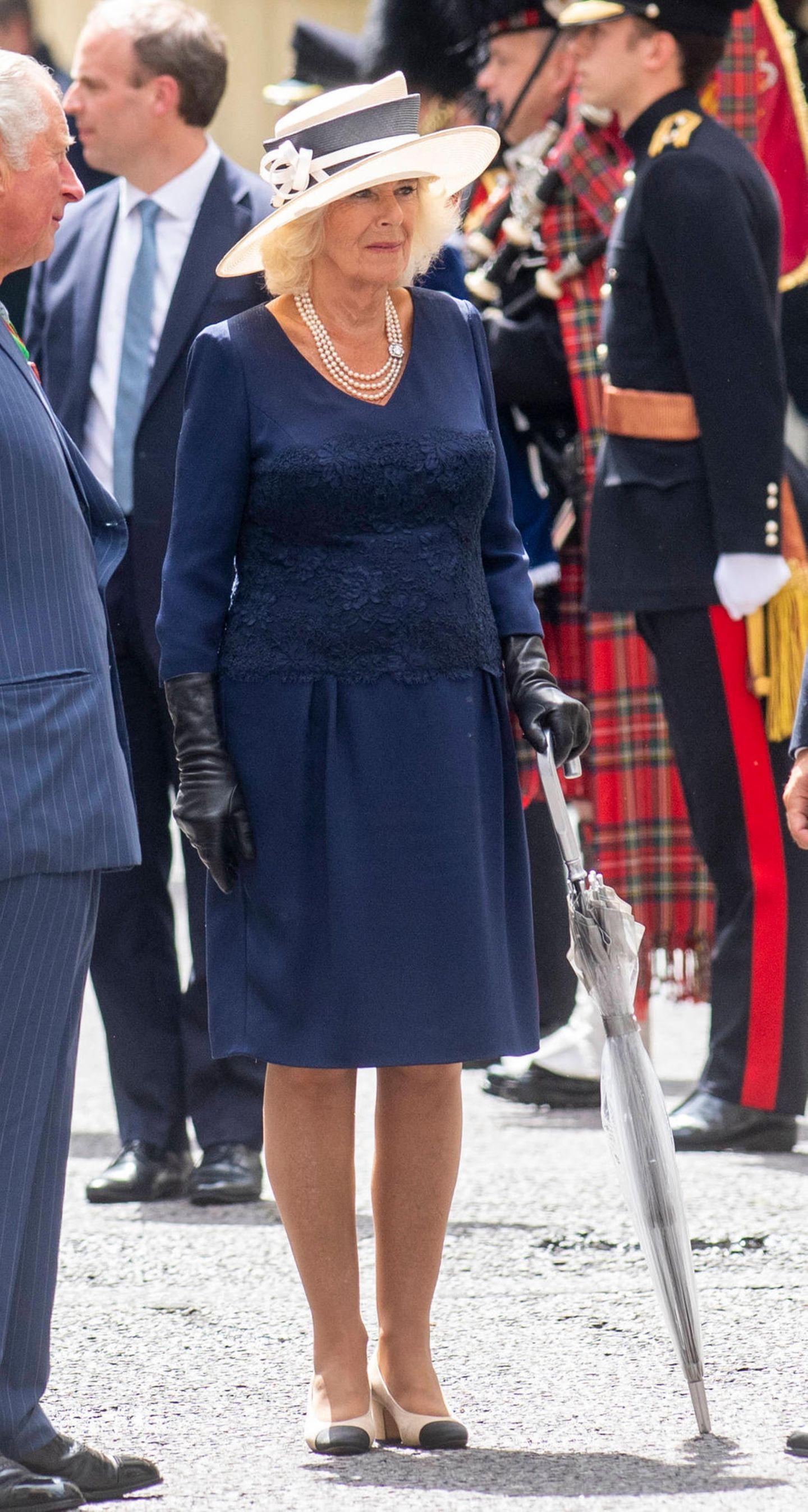 Beim Empfang vonEmmanuel Macron in London zeigte sich Herzogin Camilla von ihrer elegantesten Seite: Ein dunkelblaues Spitzenkleid kombiniert sie zu Hut, Perlenkette, Lederhandschuhen und Chanel-Pumps. Très chic!