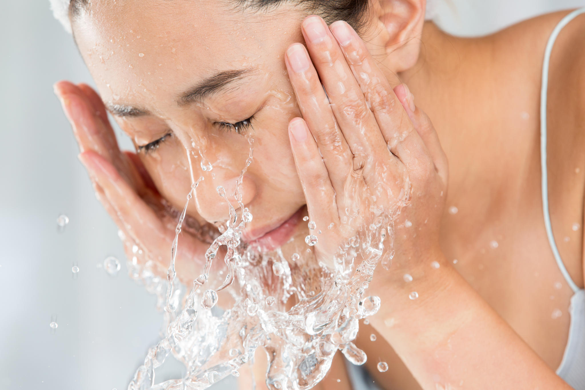 Hautausschlag im Gesicht: Frau reinigt ihr Gesicht.