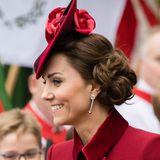 """Kopfbedeckung und kunstvoll hochgestecktes Haar geht nicht? Geht doch! Herzogin Kate präsentiert beim """"Commonwealth Day""""-Gottesdienst im März 2020 eine Frisur, die seinesgleichen sucht: leichte Locken, die voluminös zu einem Chignon im Nacken geknotet sind."""