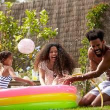 Sommerurlaub, Urlaub zu Hause, Kinder sind im Plantschbecken im Garten