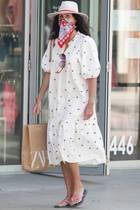 """Auf dem Weg zum Modegeschäft Zara in Los Angeles, mit einer Zara-Tüte in der Hand und in einem Zara-Kleid: Ob US-Schauspielerin Minnie Driver (""""Good Will Hunting"""") verrückt nach der spanischen Modekette ist? Ein gutes Händchen bei ihrer Kleiderwahl hat sie jedenfalls bewiesen. Ihr weißes, luftiges Sommerkleid mit Ballonärmeln und Blumenstickereien kombiniert die 50-Jährige mit lässigen Accessoires wie Hut, Flip Flops und als Highlight: ein rot-gemustertes Bandana-Tuch als Mundschutz. Bravo, Minnie!"""